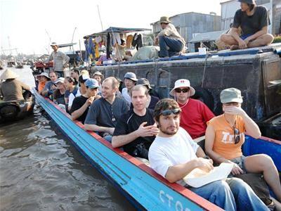 Du khách nước ngoài tại chợ nổi Cái Răng không được trang bị áo phao trong khi tàu chở quá tải.