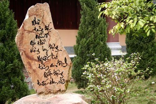 Thư pháp trên đá giữa cỏ cây hoa lá