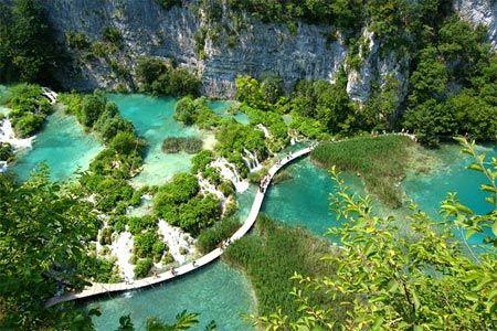 Hồ Plitvice tại Croatia được chia thành hai lưu vực bởi một con đập dài và phủ đầy bóng cây xanh.